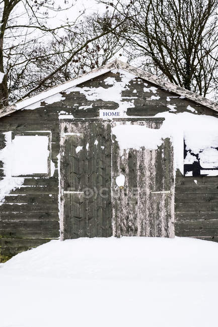 Exterior view of grey wooden garden shed with snow-covered windows. — Photo de stock