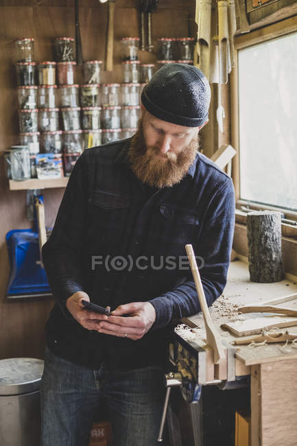 Bearded man wearing black beanie standing next to workbench in workshop, checking mobile phone. — Stock Photo