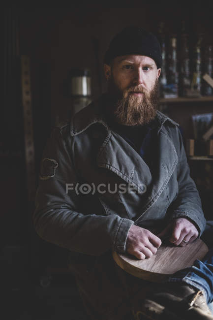 Bearded man wearing black beanie sitting in workshop, holding piece of wood, looking in camera. — Stock Photo