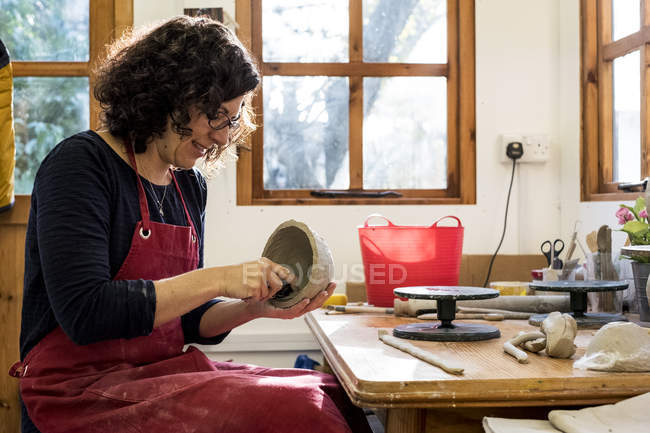 Woman in red apron sitting in ceramics workshop and working on small clay bowl. — Foto stock