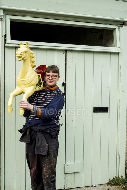 Woman carrying traditional wooden painted carousel galloper horse from merry-go-round on shoulder outside workshop — Stock Photo