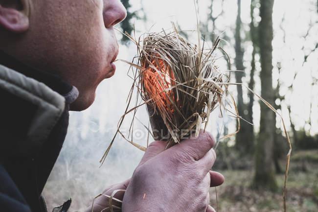 Nahaufnahme eines Mannes, der auf Strohbündel pustet und Feuer entzündet. — Stockfoto
