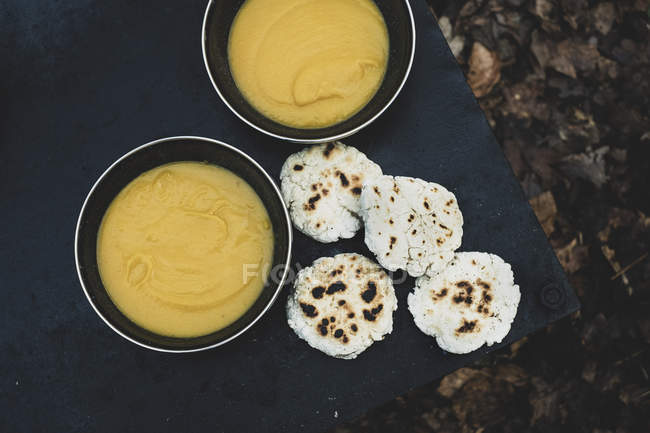 High angle close-up of freshly made bread buns and bowls of soup over campfire. — Foto stock