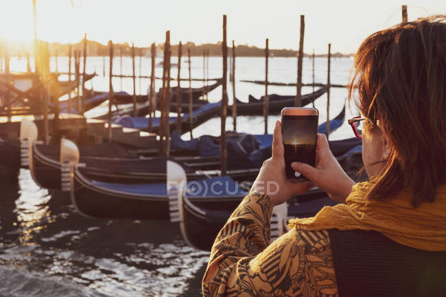 Close-up of woman taking picture of gondolas moored in Canale Grande in Venice, Veneto, Italy. — Stock Photo
