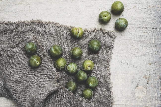 Primer plano de ángulo alto de greengages frescos sobre tela gris . - foto de stock