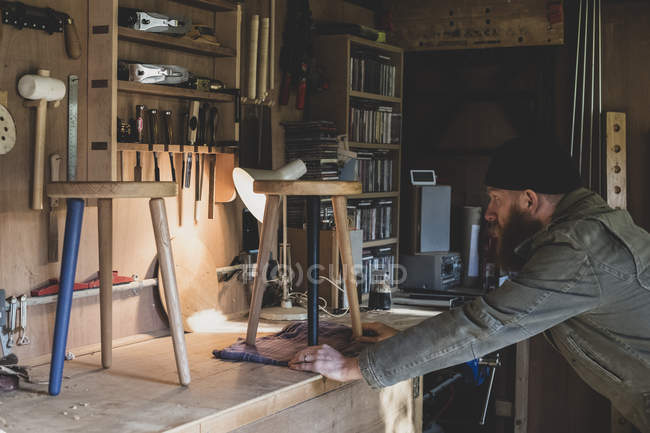 Bearded man wearing black beanie standing at workbench in workshop, examining wooden stool. — Stock Photo