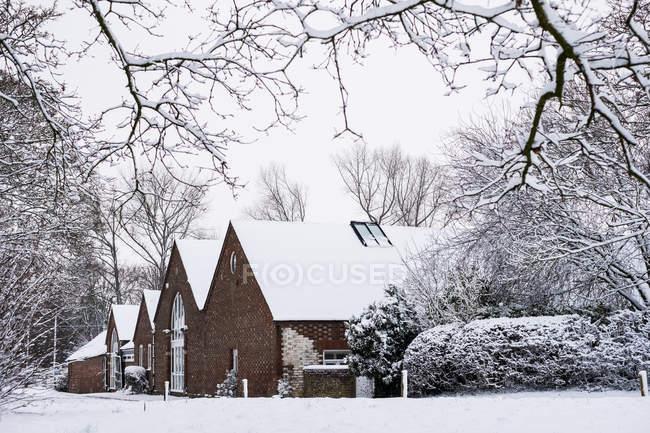 Vista exterior de casas de campo do tijolo vermelho com os telhados Snow-covered ao longo da estrada rural. — Fotografia de Stock