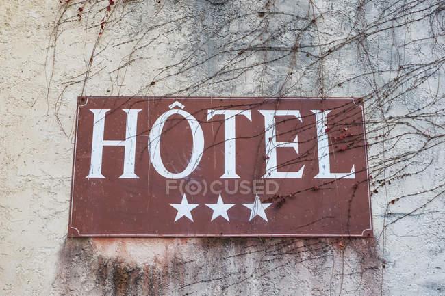 Gros plan de l'enseigne de l'hôtel trois étoiles sur le mur gris avec des brindilles d'arbres nus . — Photo de stock