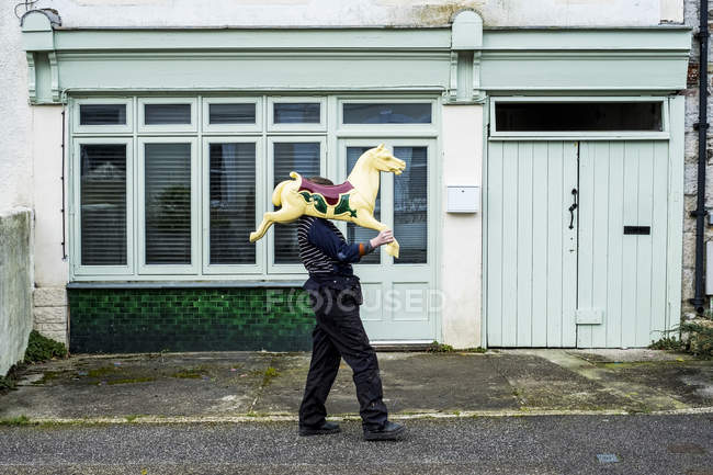 Woman carrying traditional wooden horse from merry-go-round on shoulder. — Stock Photo