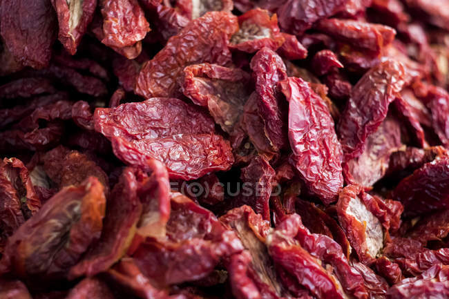 Close-up of dried red tomatoes at food market stall. — Stock Photo