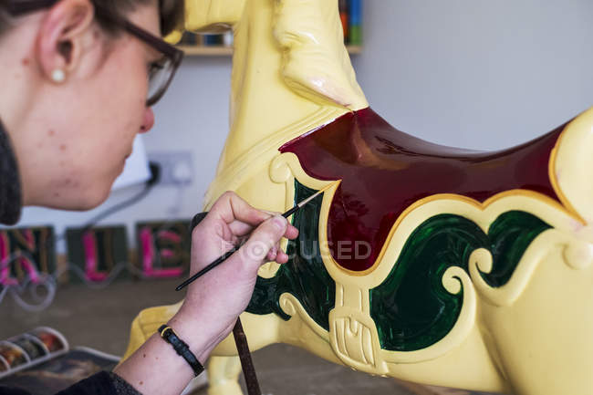 Close-up of woman in glasses in workshop painting traditional wooden horse from merry-go-round. — Stock Photo