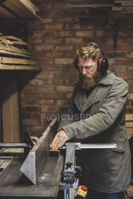 Bärtiger Mann steht in Werkstatt, trägt Ohrenschutz, bearbeitet Stück Holz. — Stockfoto