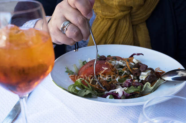 Close-up of woman sitting at cafe table and holding fork in mixed salad and glass of chilled wine. — Stock Photo