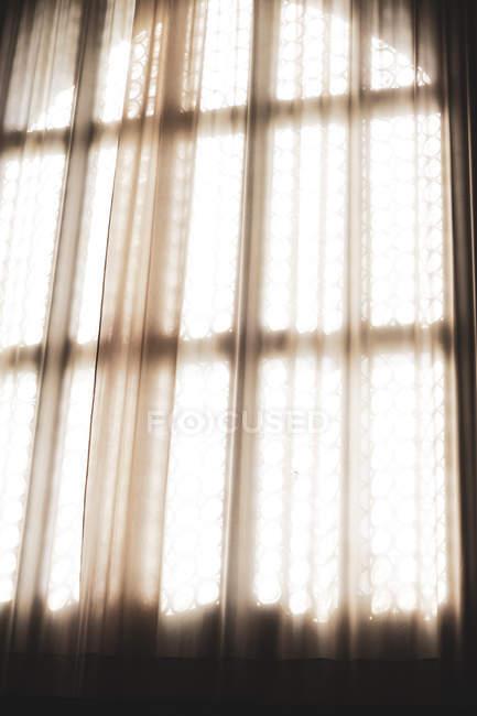 Primo piano della luce solare che filtra attraverso la tenda della rete davanti alla finestra di vetro al piombo . — Foto stock