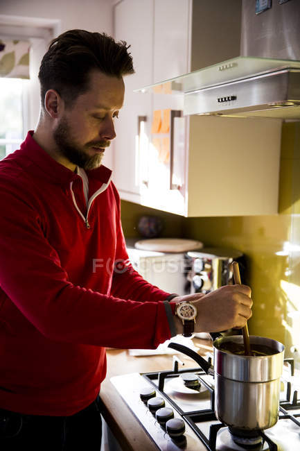 Man standing in domestic kitchen and stirring candle wax. — Stock Photo