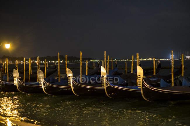 Освітлені гондол пришвартовані в Канале Гранде у Венеції, Італія, вночі та видом на воду лагуни — стокове фото