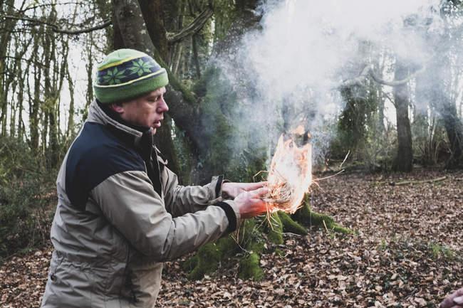 Mann steht im Wald und hält brennendes Strohbündel in der Hand, das Feuer entfacht. — Stockfoto