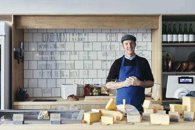 Fromager mâle derrière le compteur arrangé avec la variété des fromages — Photo de stock