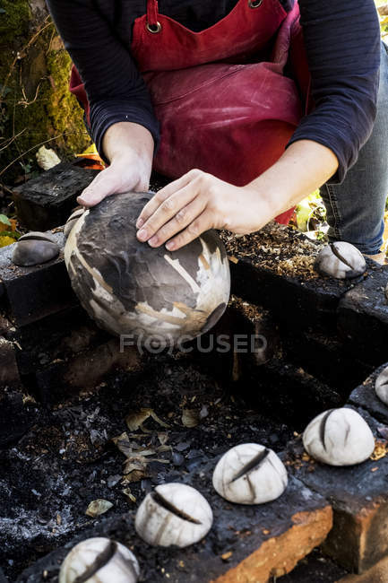Close-up of ceramic artist sitting next to outdoor smoke fire pit and working on vase. — Stock Photo