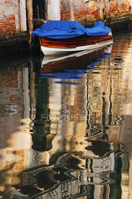 Reflection of building and boat on water in canal of Venice, Italy — стокове фото