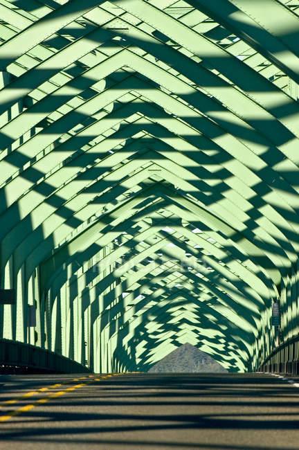 Estrutura de metal verde sobre estrada com sombras, Oregon, Estados Unidos — Fotografia de Stock