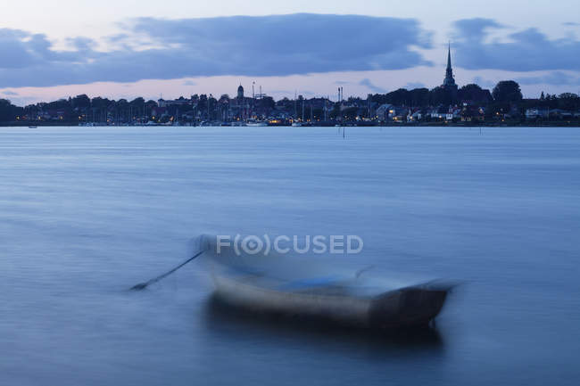 Motion blur with boat moored offshore in calm water with city skyline in distance with tall buildings and lights, Copenhagen, Denmark — Stock Photo