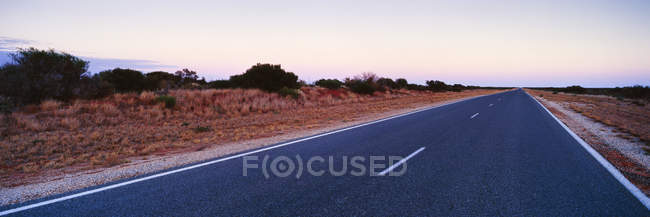 Esvazie a estrada de duas pistas no alvorecer no campo árido — Fotografia de Stock