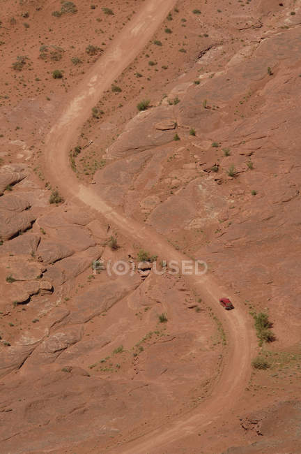 Aerial view of SUV on dirt road in rocky landscape — Fotografia de Stock