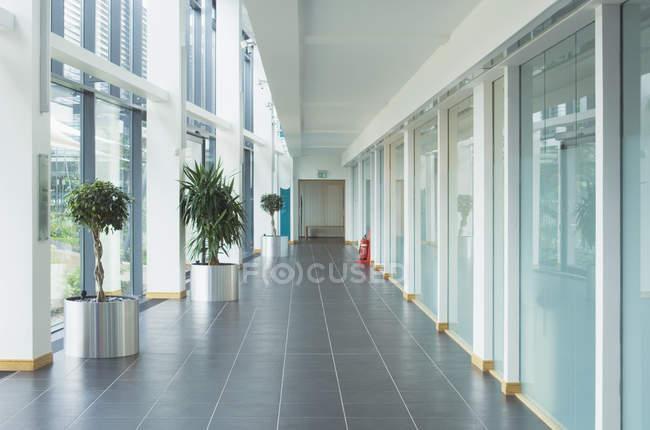 Corridor dans un immeuble de bureaux moderne avec des murs en verre — Photo de stock