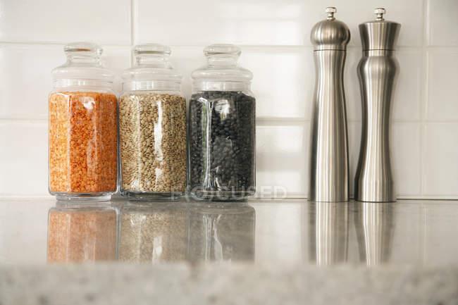 Küchentisch mit Hülsenfrüchten und Salz- und Pfefferstreuern — Stockfoto