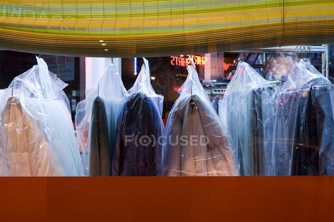 Dry-cleaned clothing in plastic bags hanging in laundry, Seattle, Washington, United States — Stock Photo