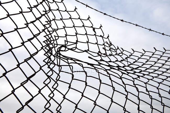 Дыра в цепи звено забор с облачным небом, крупным планом — стоковое фото