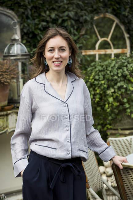 Жінка з каштанове волосся і сірий блузка стоячи на відкритому повітрі, посміхаючись в камері. — стокове фото