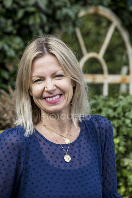 Frau mit blonden Haaren und blauem Oberteil im Freien stehend, lächelnd in der Kamera. — Stockfoto