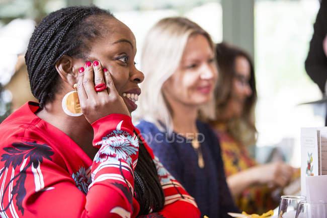 Жінка з хлібними рядами в золотих сережки і Червона кофтинка сидить за столом, слухаючи жіночих друзів уважно. — стокове фото