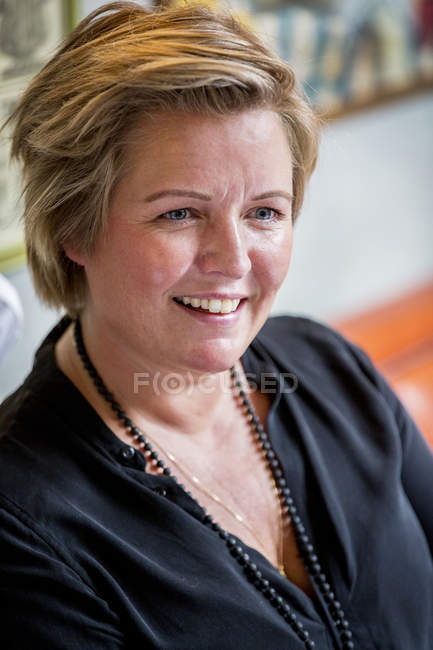 Portrait of smiling mature woman with short blonde hair in black blouse. — Stock Photo