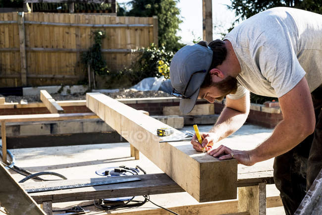 Man wearing baseball cap standing on building site, measuring and marking wooden beam. — Stock Photo