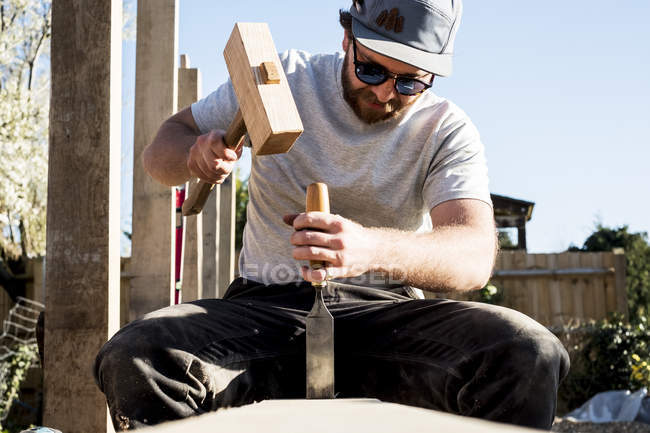 Man wearing baseball cap and sunglasses on building site, using mallet and chisel, working on wooden beam. — Stock Photo