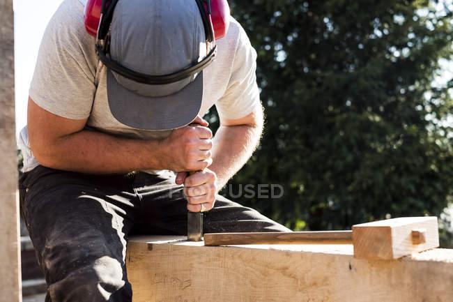 Homme utilisant la casquette de base-ball et les protecteurs d'oreille sur le chantier de construction, travaillant sur la poutre en bois. — Photo de stock