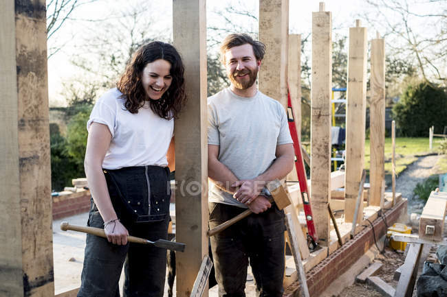 Smiling man and woman holding hand tools while standing on building site of residential building. — Stock Photo