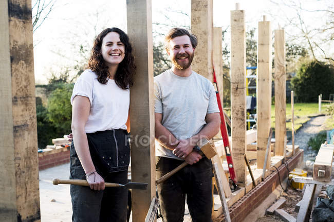 Smiling man and woman holding hand tools and standing on building site of residential building. — Stock Photo