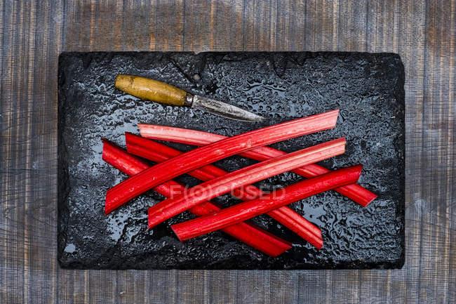 High angle close-up of rhubarb stalks and knife on black slate. — Stock Photo