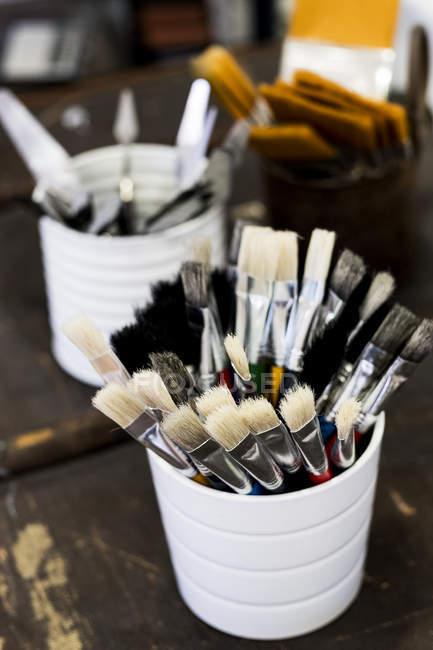 Nahaufnahme weißer Keramiktöpfe mit ausgewählten Pinseln in verschiedenen Größen. — Stockfoto
