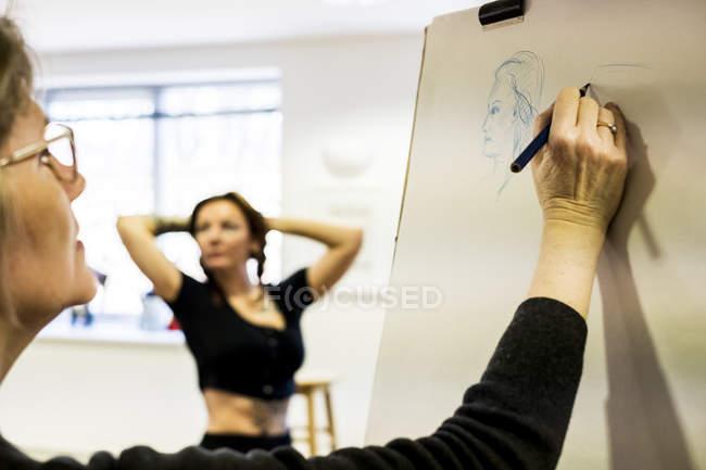 Крупний план жінки стоячи на станковий, спираючись руку з моделлю сидячи у фоновому режимі. — стокове фото