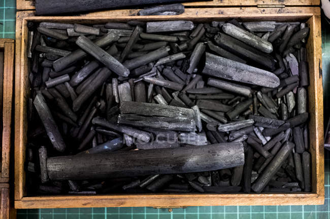 High angle close-up of wooden box with selection of charcoal sticks in different sizes. — Stock Photo
