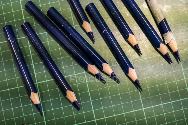 Primo piano ad alto angolo di matite blu affilate su tappetino da taglio verde . — Foto stock