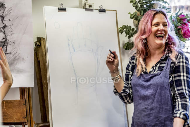 Сміється жінка в фартух, що стоїть при Станці і нанесення ручного. — стокове фото