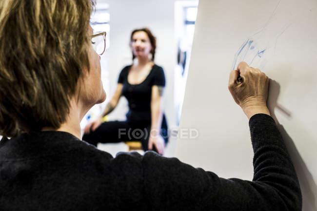 Жінка, що стоїть на мольберті і малюнок рукою в той час як модель сидить у фоновому режимі. — стокове фото