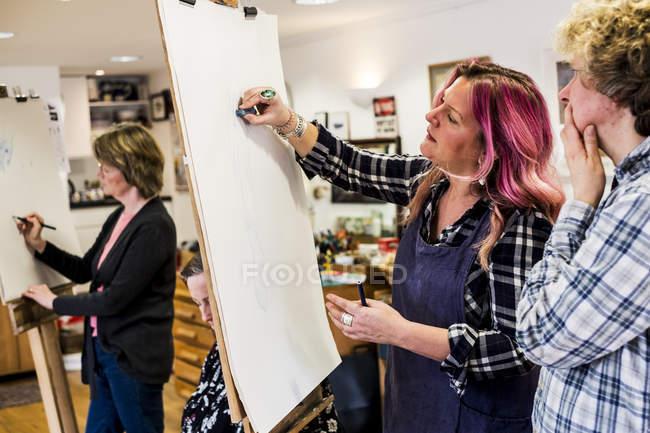 Жінка, що стоїть на станковий, малюнок людини ногу в класі малювання. — стокове фото
