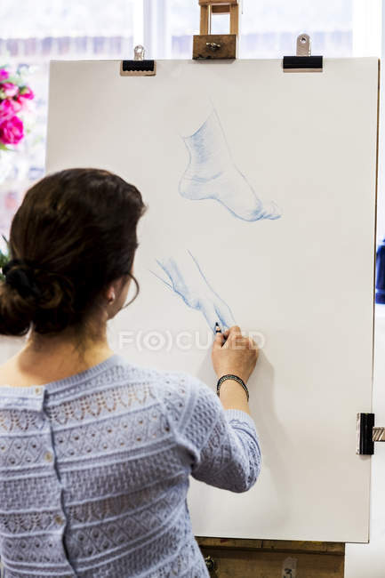 Rear view of woman standing at easel and drawing hand and foot. — Stock Photo